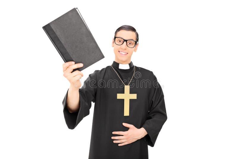 Счастливый молодой священник держа библию стоковая фотография rf