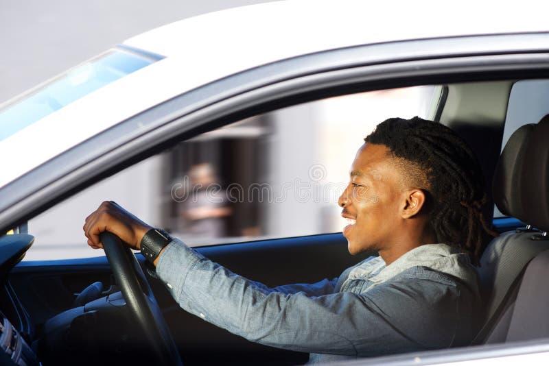 Счастливый молодой чернокожий человек управляя автомобилем стоковые фотографии rf