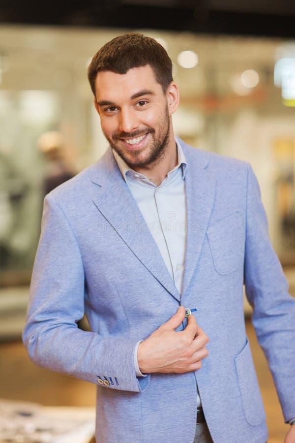 Счастливый молодой человек в куртке на магазине одежды стоковая фотография rf