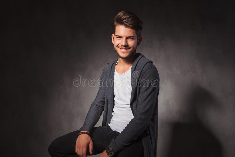 Счастливый молодой человек в предпосылке студии усмехаясь на камере стоковое изображение rf