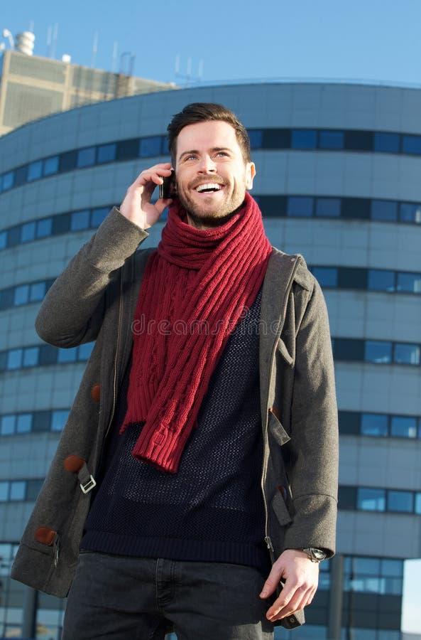 Счастливый молодой человек говоря на мобильном телефоне в городе стоковые фотографии rf