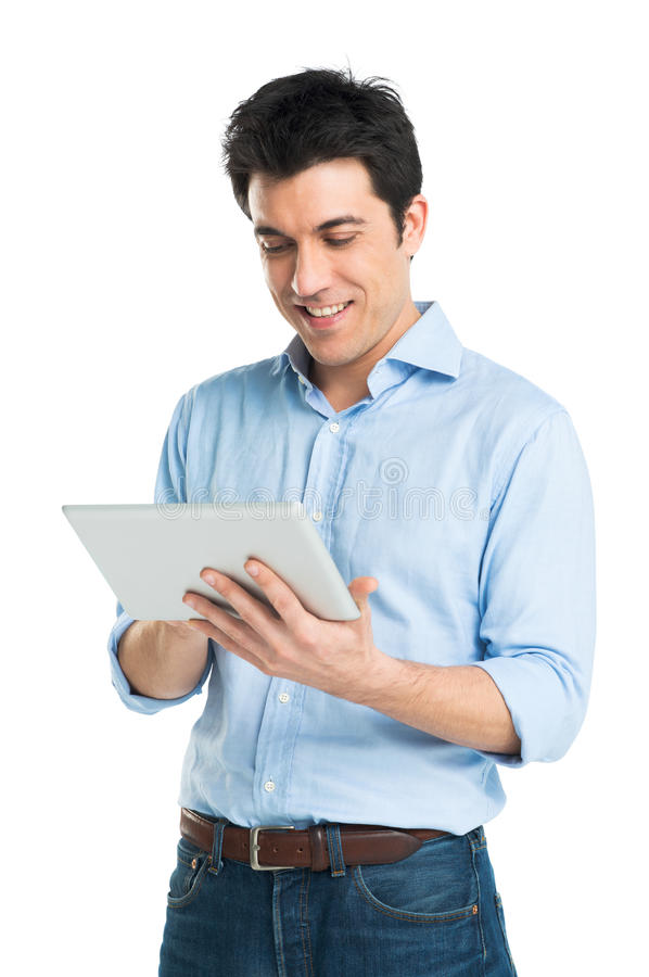 Счастливый молодой человек используя таблетку цифров стоковое изображение