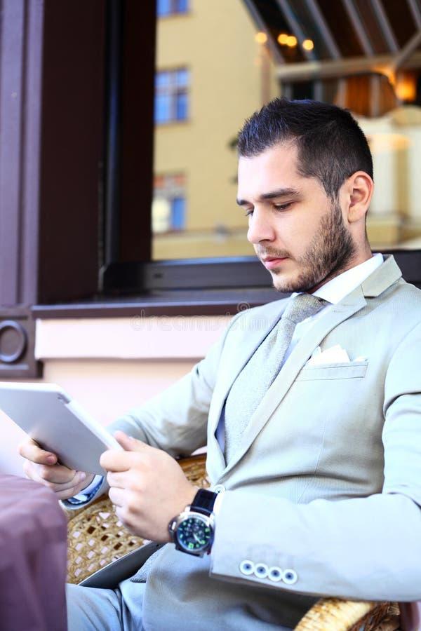 Счастливый молодой человек используя цифровую таблетку в кафе стоковые изображения rf