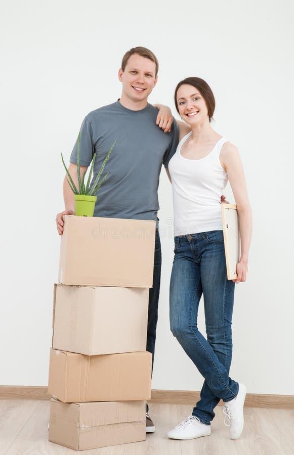 Счастливый молодой человек и женщина стоя близко картонные коробки стоковая фотография