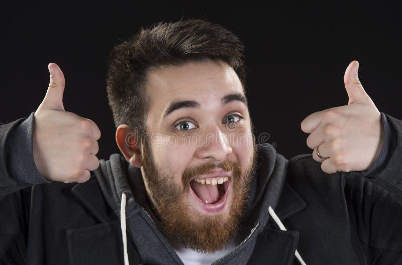 Счастливый молодой человек показывая большие пальцы руки поднимает знаки стоковая фотография rf