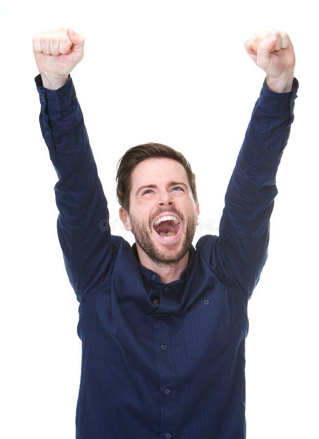 Счастливый молодой человек празднуя при поднятые оружия стоковые изображения