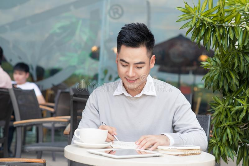Счастливый молодой человек работая на портативном компьютере во время перерыва на чашку кофе i стоковое изображение rf