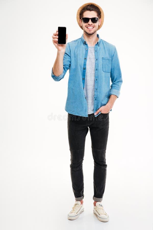 Счастливый молодой человек стоя и держа сотовый телефон пустого экрана стоковое фото