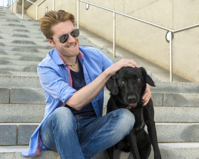 Счастливый молодой человек с его собакой стоковая фотография rf