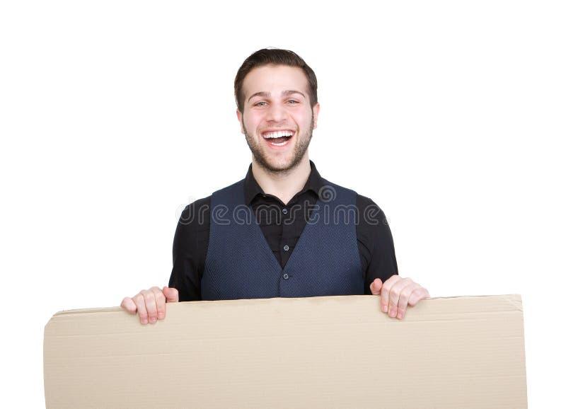 Счастливый молодой человек с пустым знаком плаката стоковая фотография rf