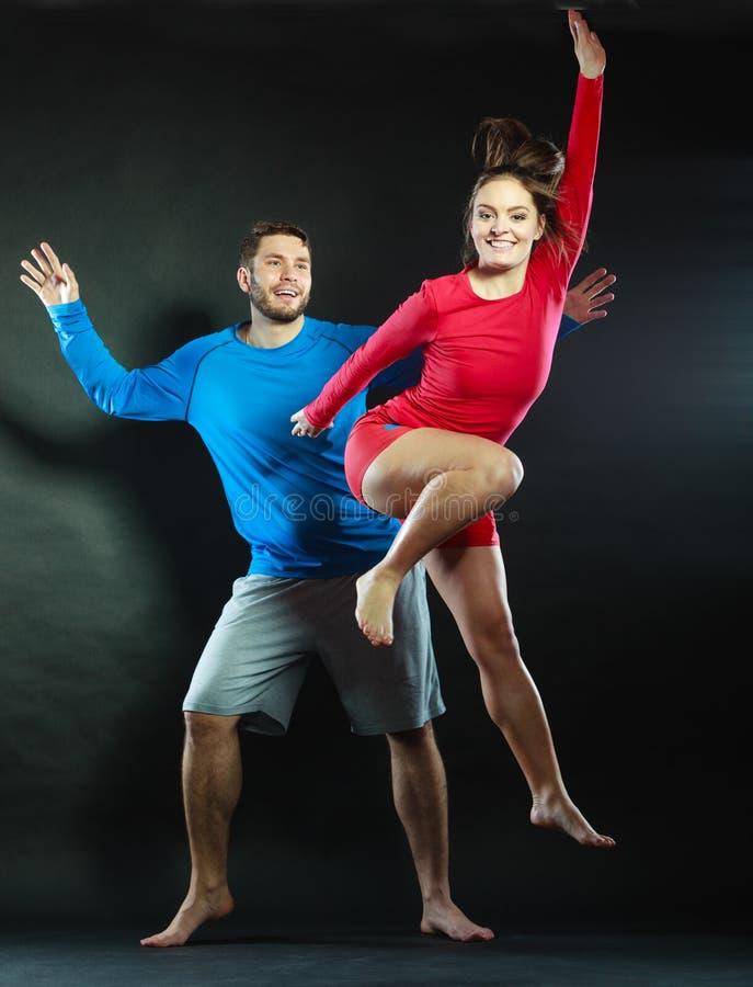 Счастливый молодые человек и женщина пар скача для утехи стоковое фото rf
