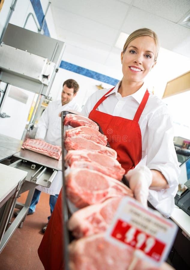 Счастливый мясник показывая поднос мяса в магазине стоковые фотографии rf