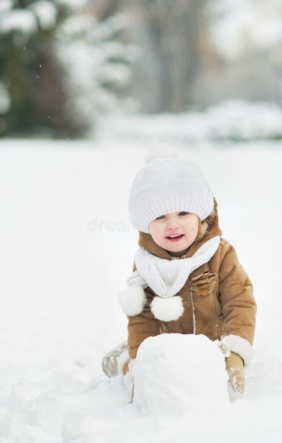 Счастливый младенец делая снежный ком для снеговика стоковая фотография rf