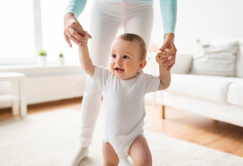 Счастливый младенец уча идти с помощью матери стоковая фотография rf