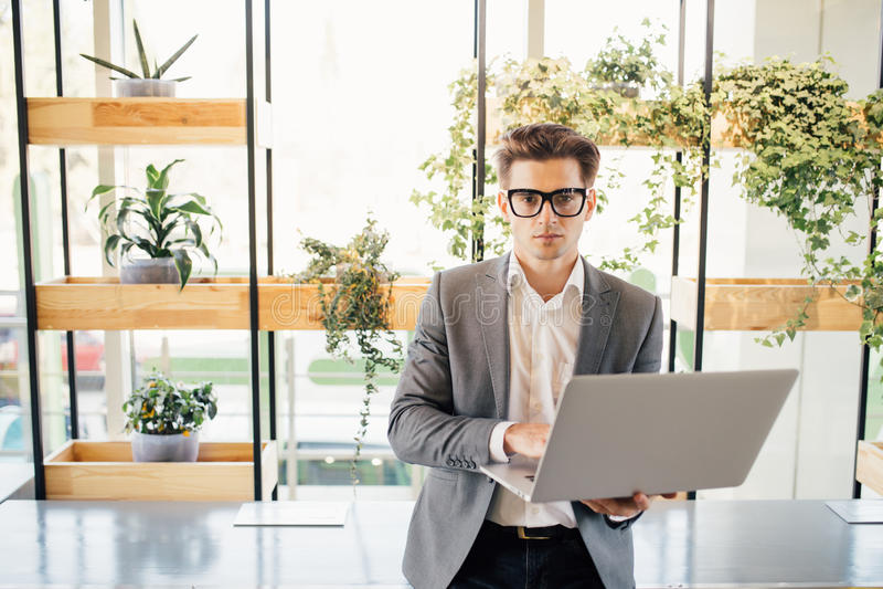 Счастливый независимый бизнесмен сидя на столе офиса с компьтер-книжкой в руках и печатать, смотря камеру стоковая фотография rf