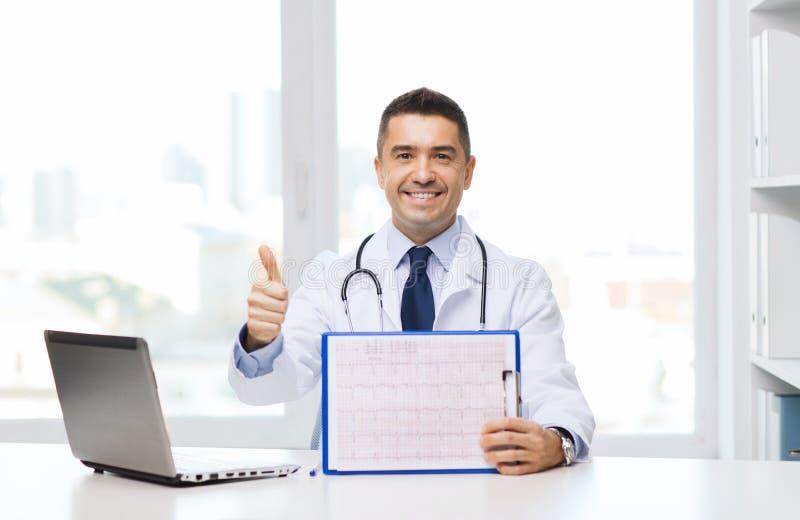 Счастливый доктор при доска сзажимом для бумаги показывая большие пальцы руки вверх стоковая фотография rf