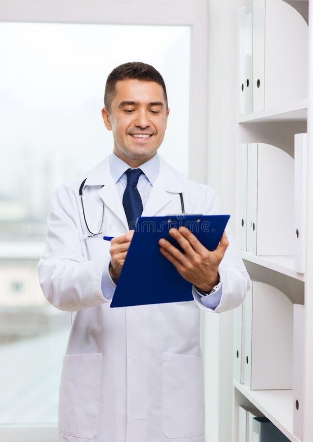 Счастливый доктор с доской сзажимом для бумаги в медицинском офисе стоковая фотография