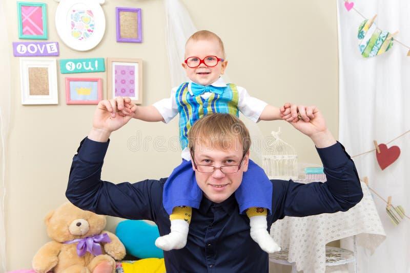 Счастливый отец держит маленького усмехаясь сына на его плечах стоковое фото rf