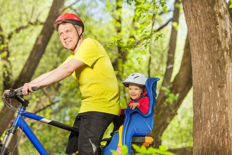 Счастливый отец и его маленькая дочь ехать велосипед стоковое изображение rf