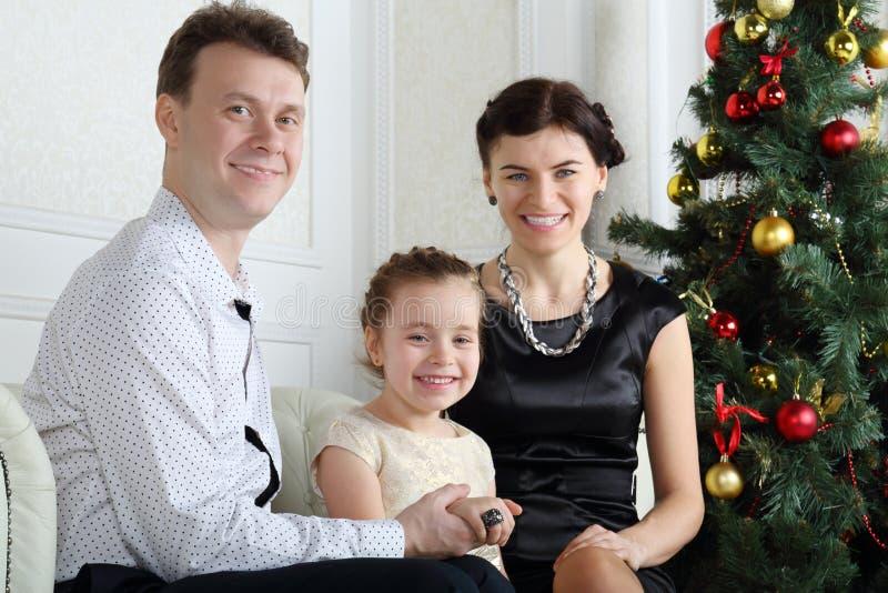 Счастливый отец, маленькая дочь с кольцом на пальце и мать сидят стоковое фото rf