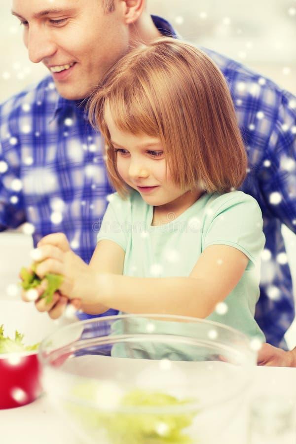 Счастливый отец при девушка делая обедающий дома стоковое изображение