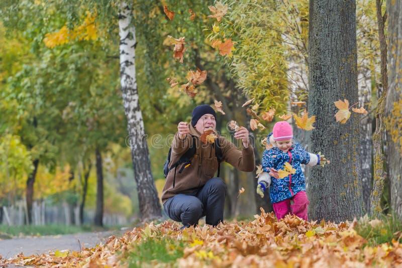 Счастливый отец при маленькая дочь меча вверх по желтым листьям осени в парке outdoors стоковое фото