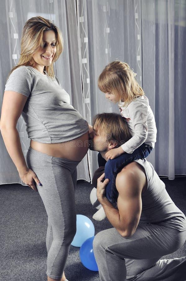 Счастливый папа при дочь на его плечах целуя его wife's belly стоковые изображения
