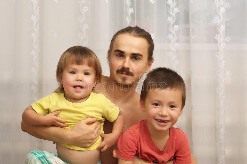 Счастливый папа с 2 шаловливыми детьми стоковое фото rf