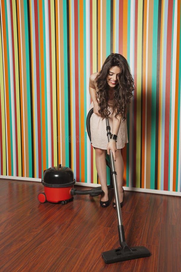 Счастливый паркет чистки молодой женщины используя пылесос стоковое фото