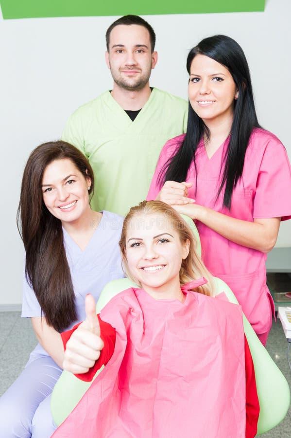 Счастливый пациент и зубоврачебная команда стоковые изображения rf