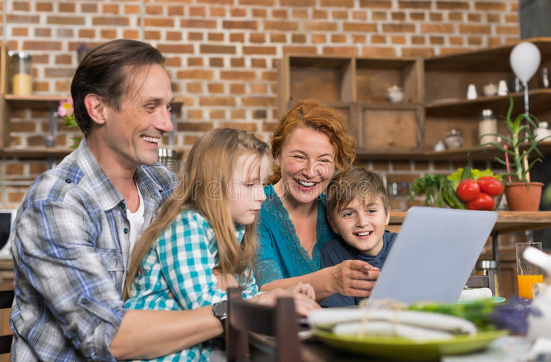 Счастливый портативный компьютер пользы семьи сидя на кухонном столе, родителях с сыном и интернете дочери занимаясь серфингом стоковое фото rf