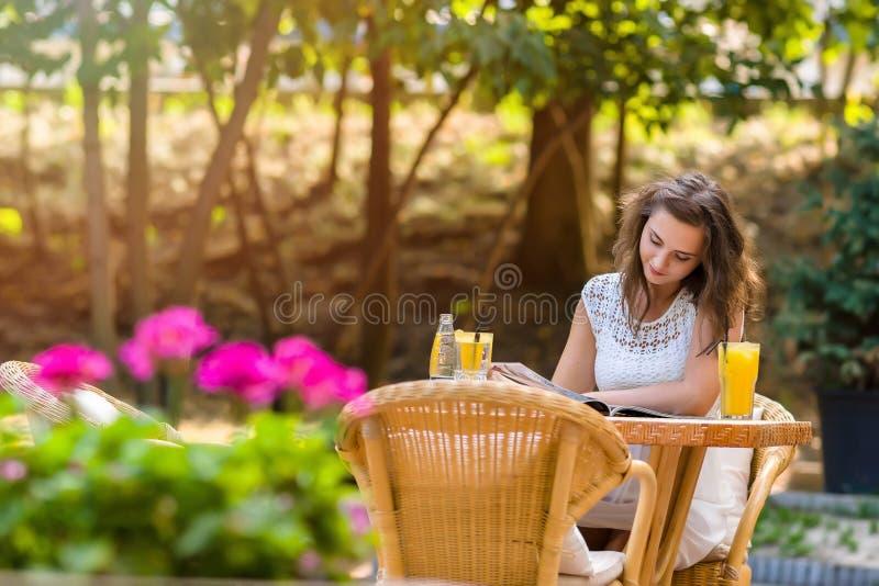 Счастливый, положительный, красивый, девушка элегантности сидя на кафе ставит на обсуждение outdoors стоковое фото rf