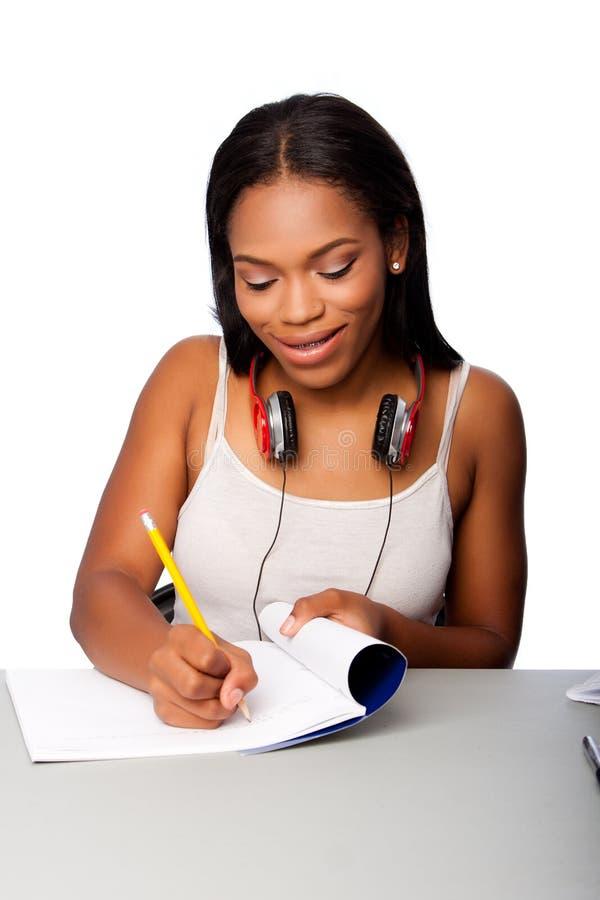Счастливый подростковый студент делая домашнюю работу стоковые изображения rf