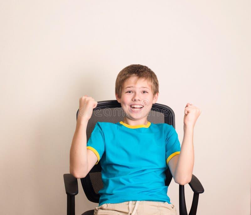 Счастливый предназначенный для подростков мальчик в выигрывая представлении Ребенк успеха в happ стула офиса стоковое изображение