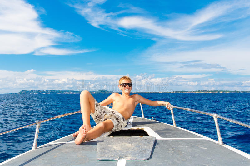Счастливый предназначенный для подростков мальчик в солнечных очках на яхте Тропическое море в b стоковое фото rf
