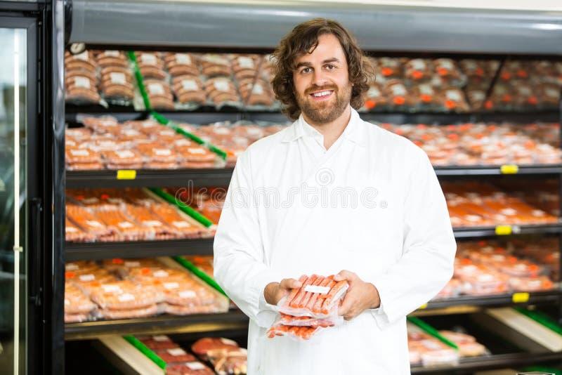 Счастливый продавец держа пакеты мяса на счетчике стоковое изображение