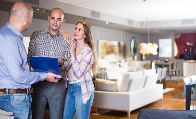 Счастливый продавец показывая клиентам каталог продукта стоковые изображения