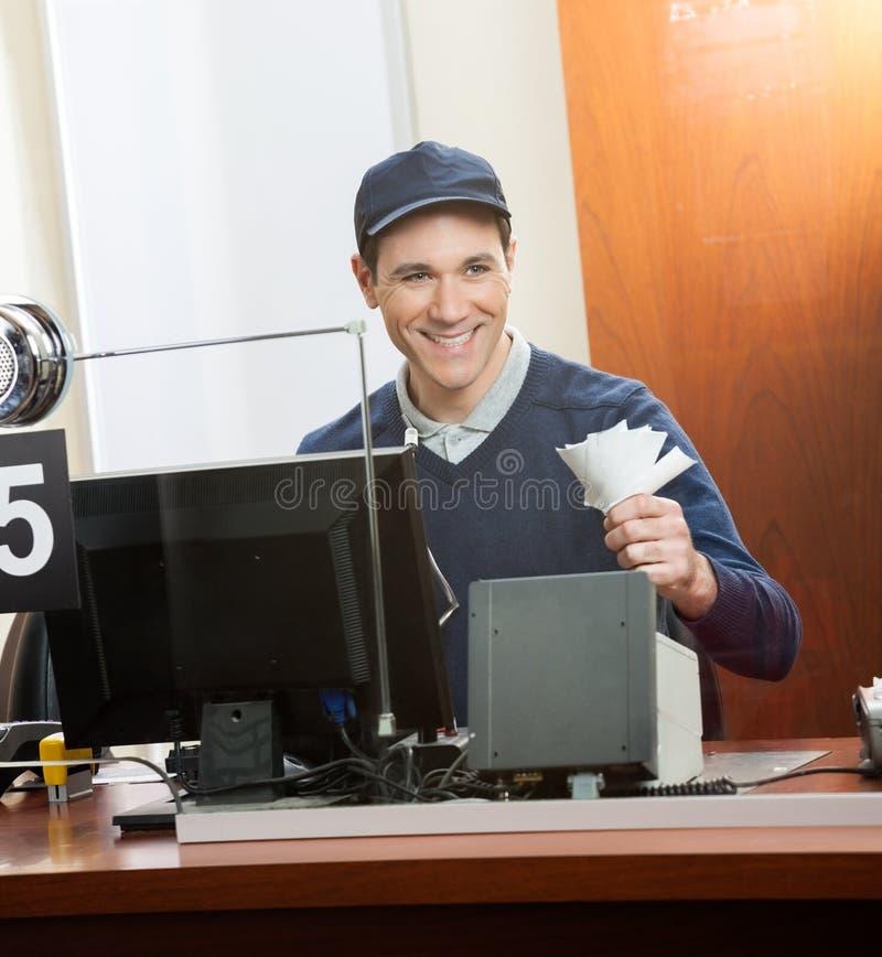 Счастливый работник держа билеты на кассовом сборе стоковое изображение rf