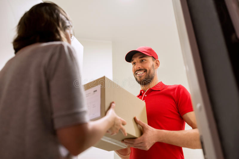 Счастливый работник доставляющий покупки на дом давая коробку пакета к клиенту стоковые фото