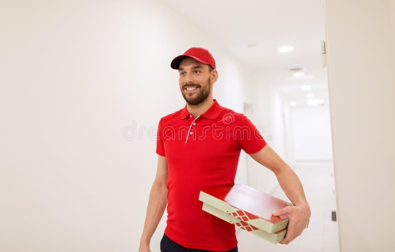 Счастливый работник доставляющий покупки на дом с коробками пиццы в коридоре стоковое изображение