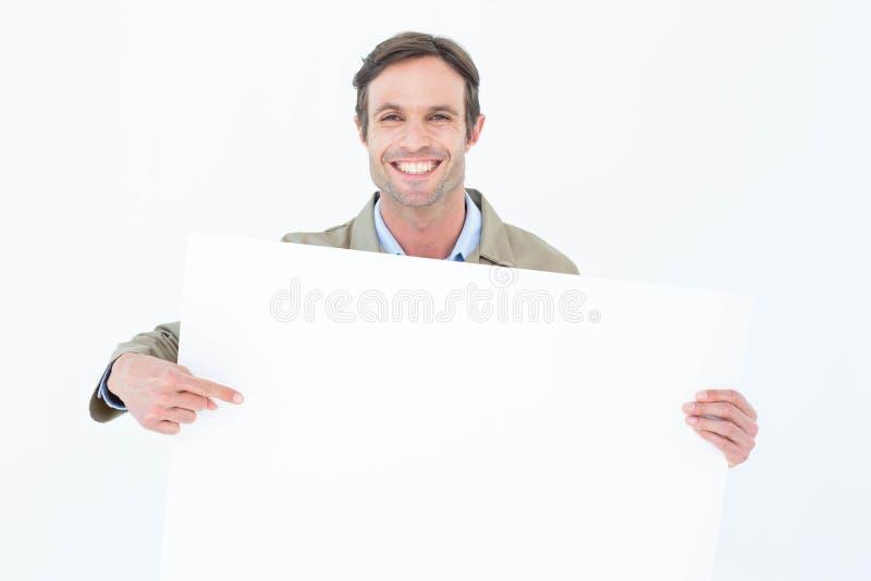 Счастливый работник доставляющий покупки на дом указывая на пустую афишу стоковое изображение rf