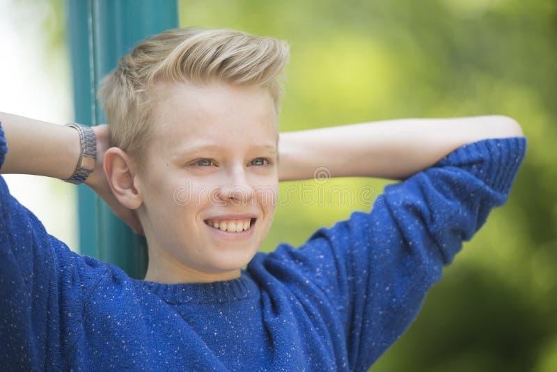 Счастливый расслабленный усмехаясь мальчик подростка внешний стоковое фото rf