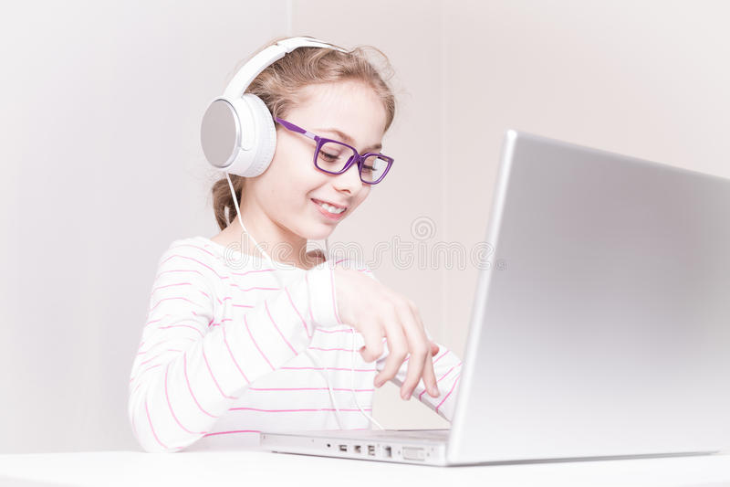 Счастливый ребенк девушки ребенка в наушниках используя портативный компьютер стоковое фото