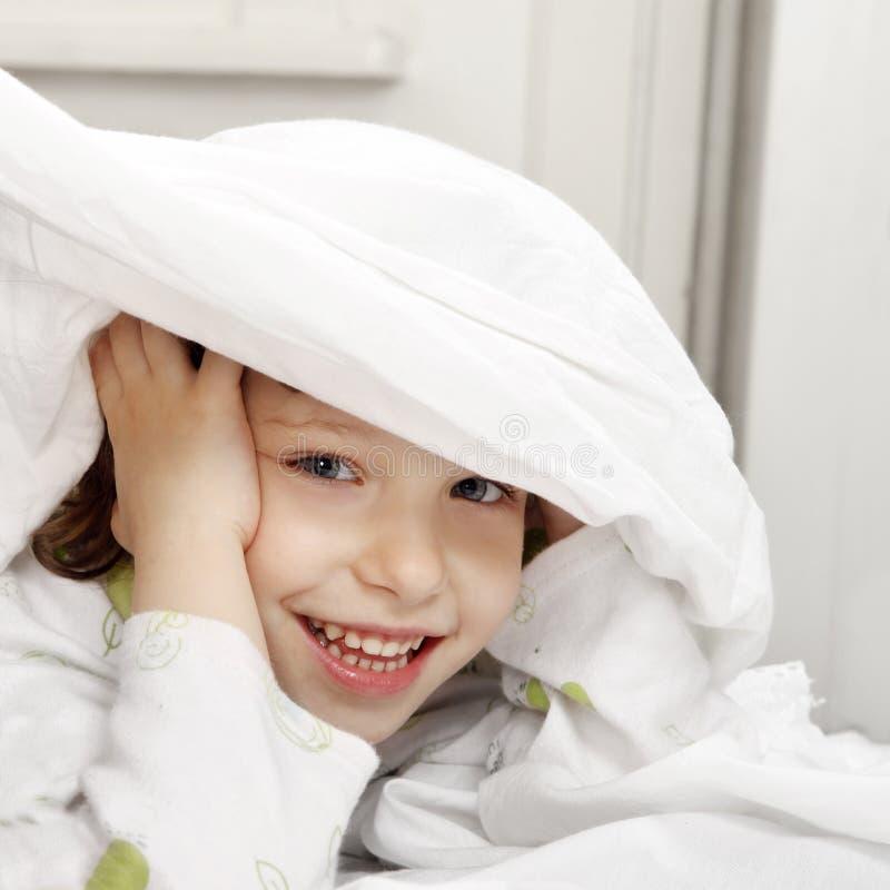 Счастливый ребенок в кровати стоковые изображения rf