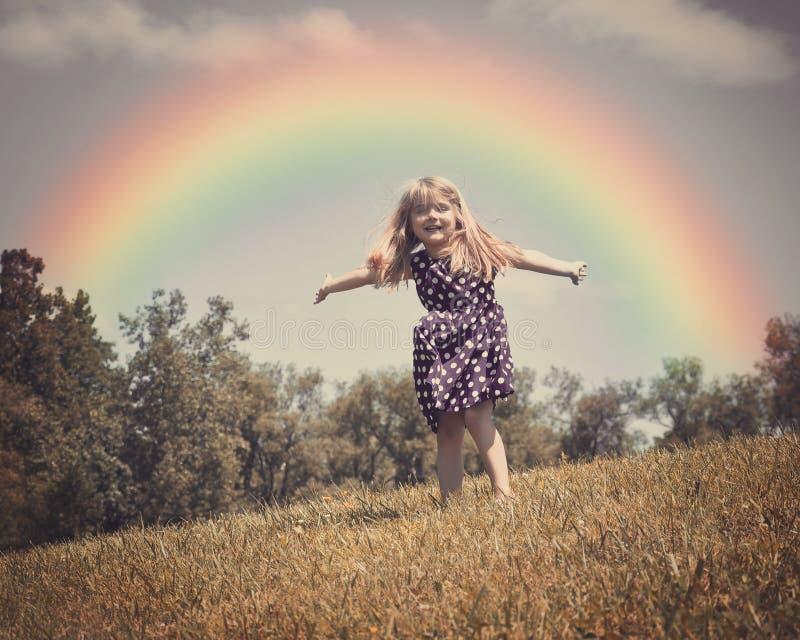 Счастливый ребенок в поле природы с радугой стоковое изображение rf