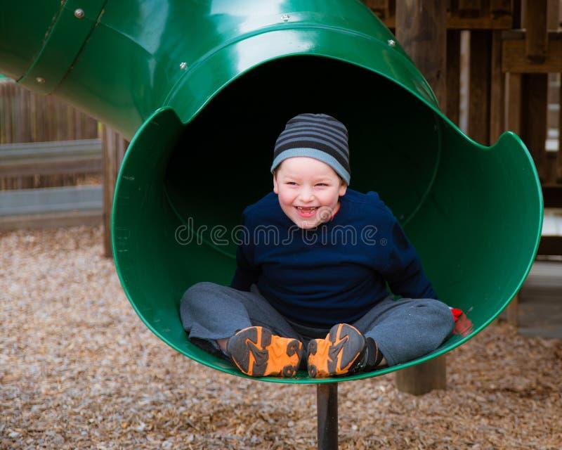 Счастливый ребенок ехать вниз с скольжения стоковая фотография rf