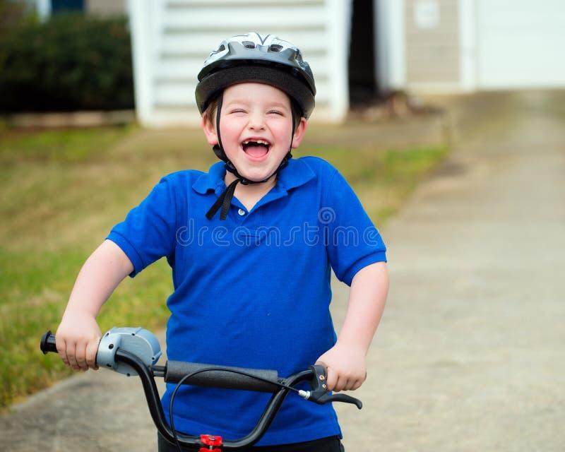 Счастливый ребенок ехать его велосипед стоковое фото