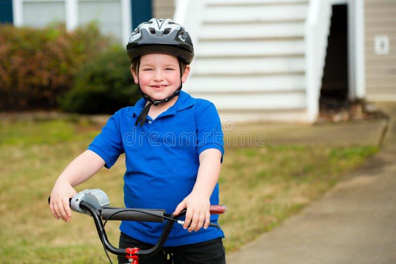 Счастливый ребенок ехать его велосипед стоковое фото rf
