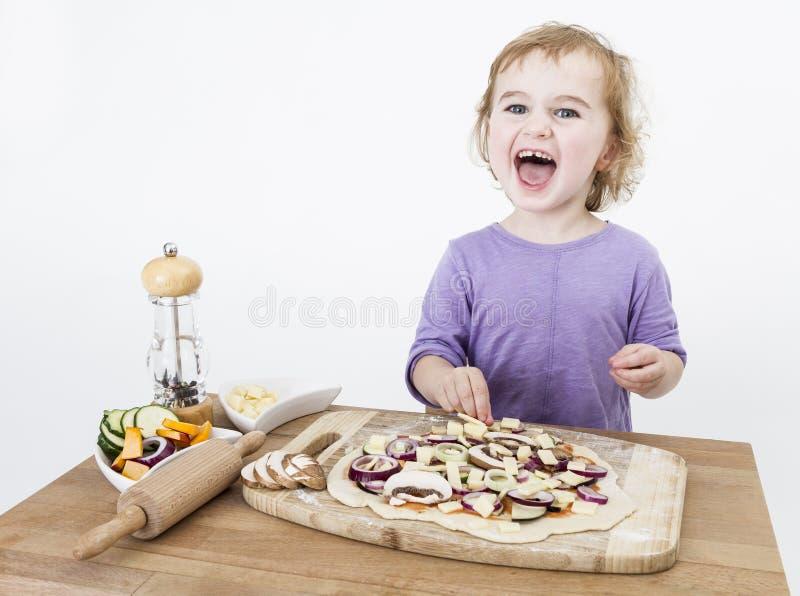 Счастливый ребенок делая пиццу стоковые фотографии rf