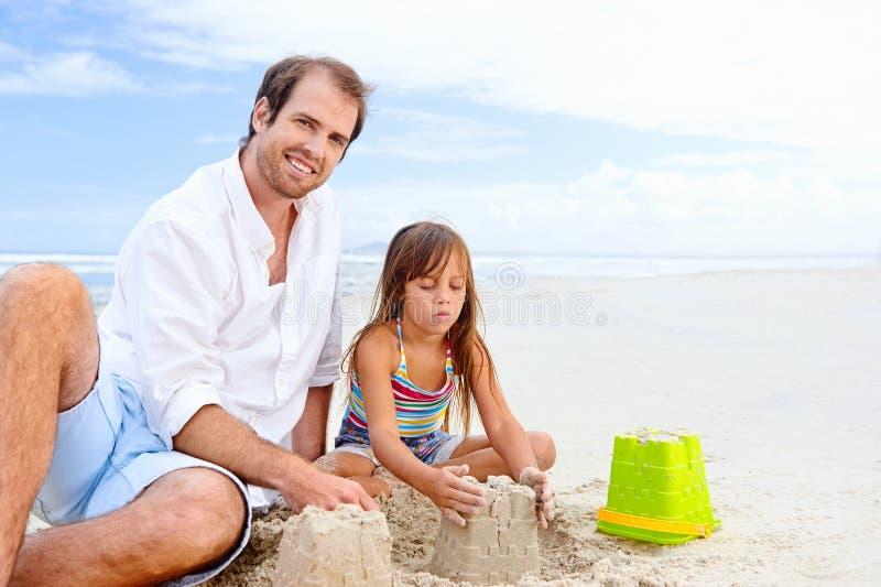Счастливый ребенок замка песка стоковые фотографии rf